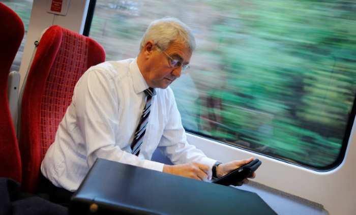 man working on the train and checking his mobile phone