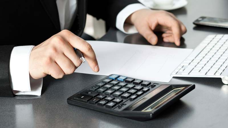 accountant with a pen in hand and calculator