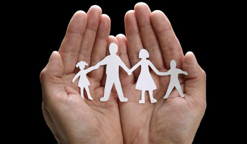 life insurance, hands holding a cut paper representing a family