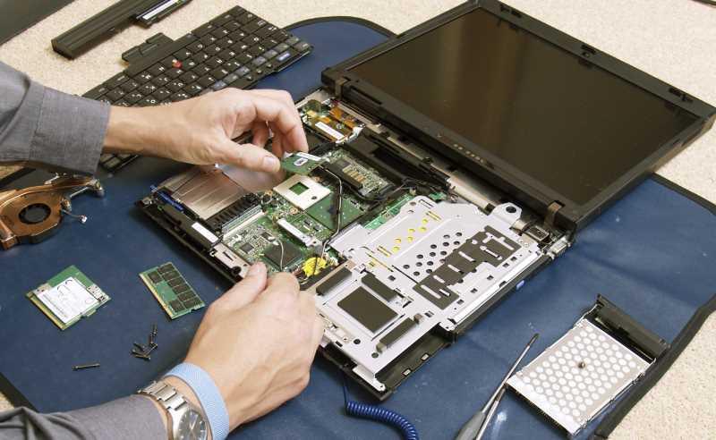 computer repair business, hands repairing an open laptop