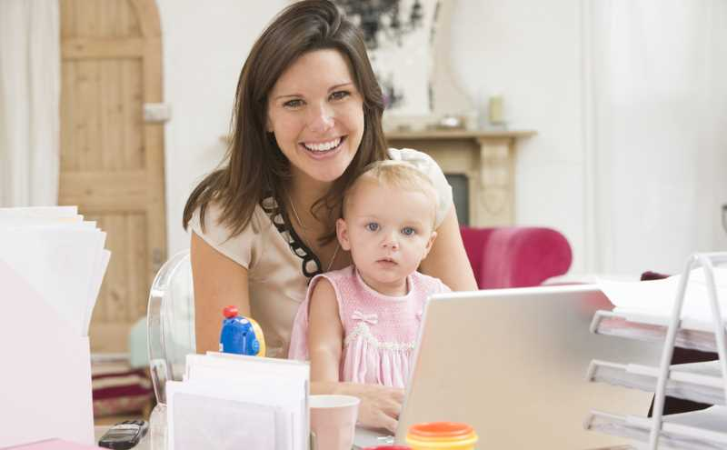 work from home mum, typing on computer with baby on her knees