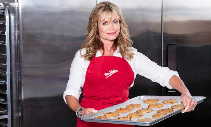 Debbi Fields the founder of Mrs Fields cookies Chain store wearing company apron and holding a tray of cookies