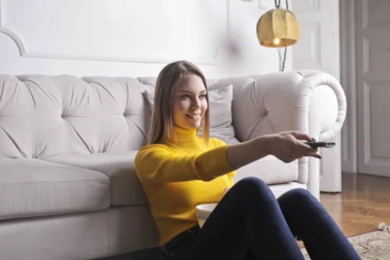 woman using remote tv control