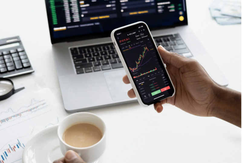 hand holding smartphone in front of laptop showing stocks charts
