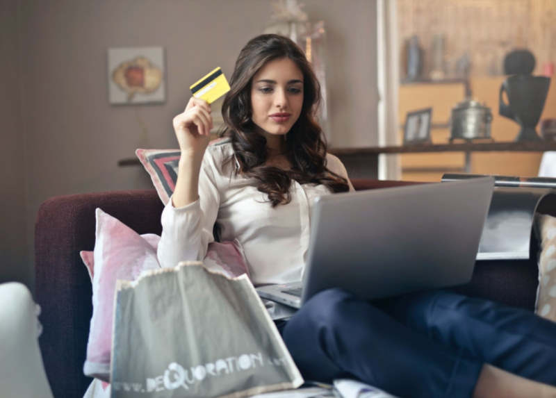 woman shopping on line with credit card in right hand