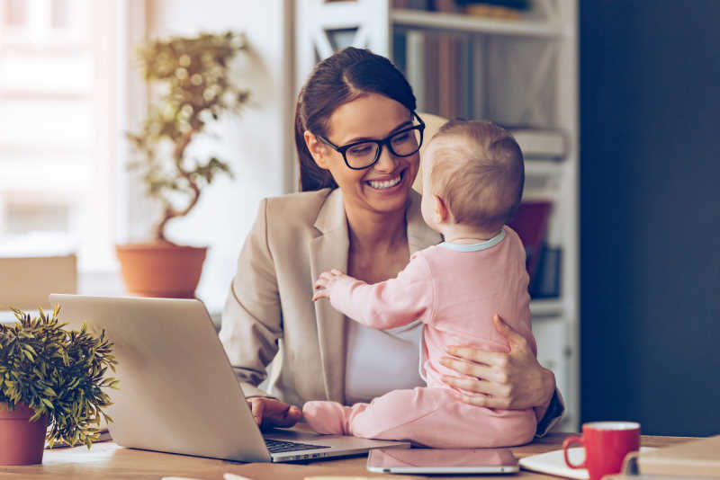 woman working on her laptop with a baby