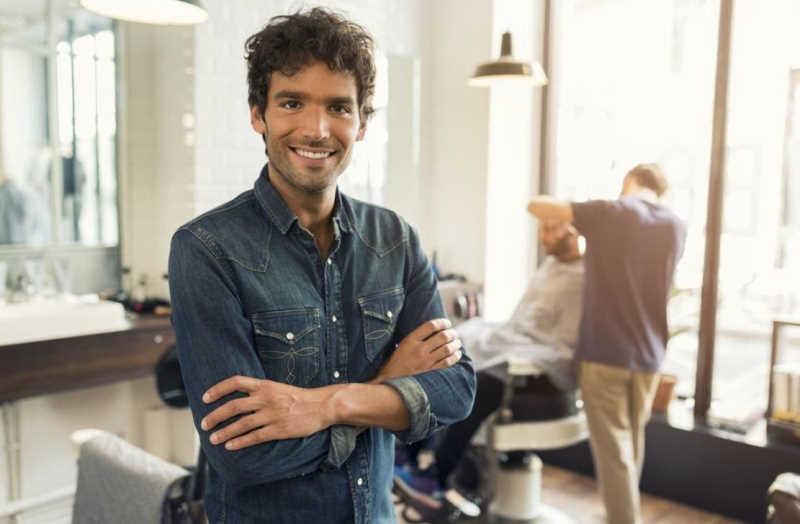 smiling man arms crossed in barber shop
