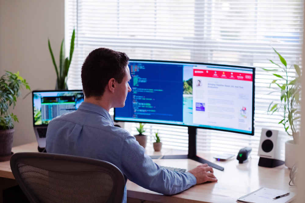man sitting in front of 2 screen in home office
